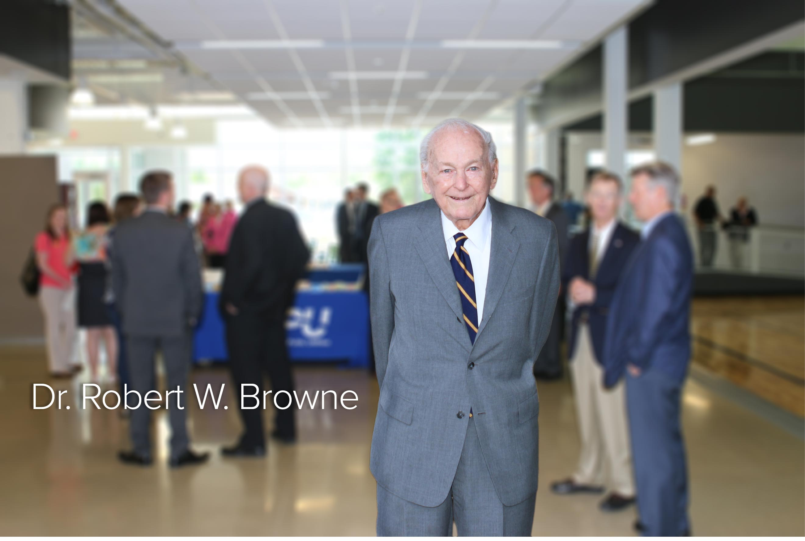 Robert W. Browne posing for a picture with people in the background