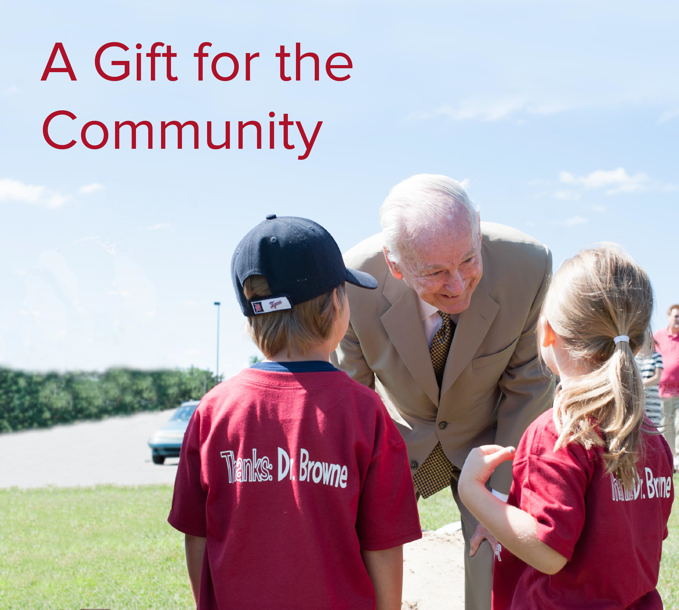 Robert W. Browne talking to two young children with text that reads A Gift for the Community