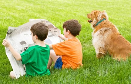 Two boys reading a newspaper while sitting in the grass with a dog sitting next to them.